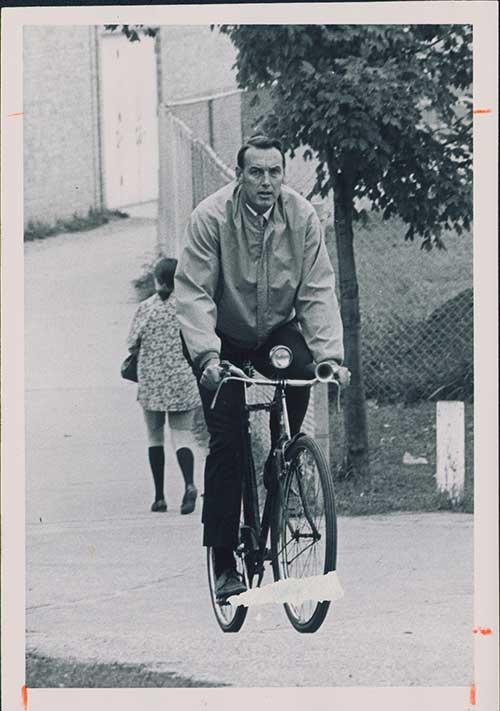 Paul Lauritzen rides a bike through campus.