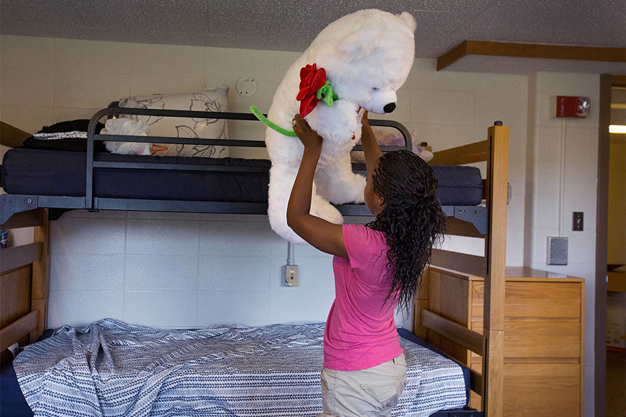 Student lifts large teddy bear in dorm room.
