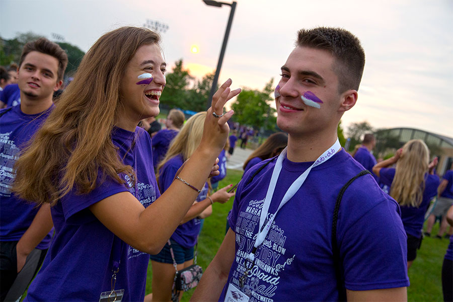 Students apply facepaint during a welcome rally.