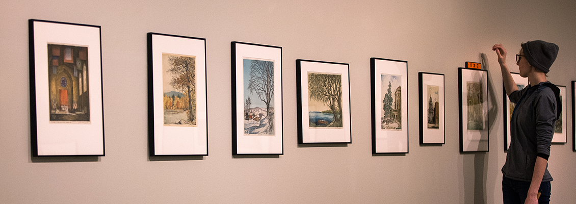 Student hanging artwork in the Crossman Gallery
