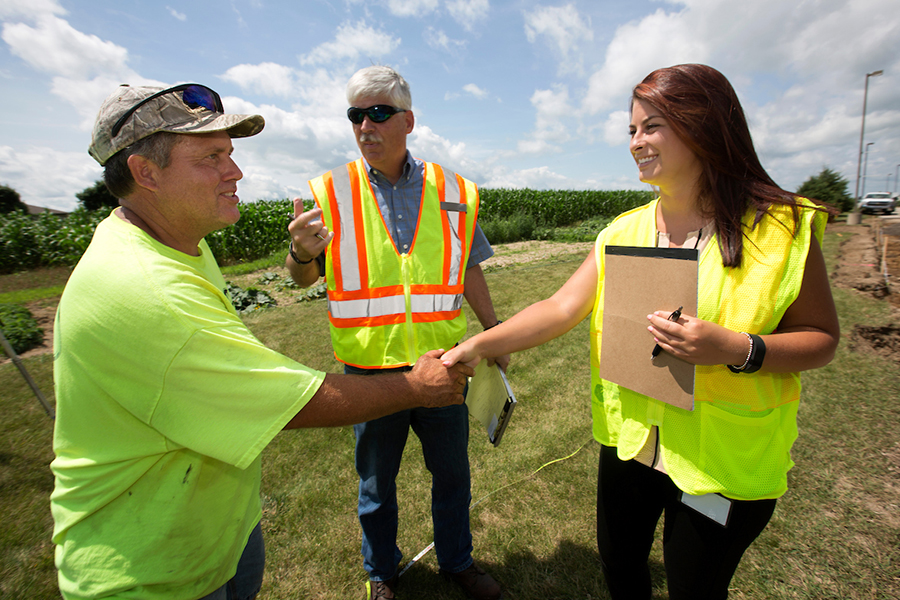 Morgan Drewek shakes hands with the foreman of the construction site being inspected as mentor David Kapitan looks on.