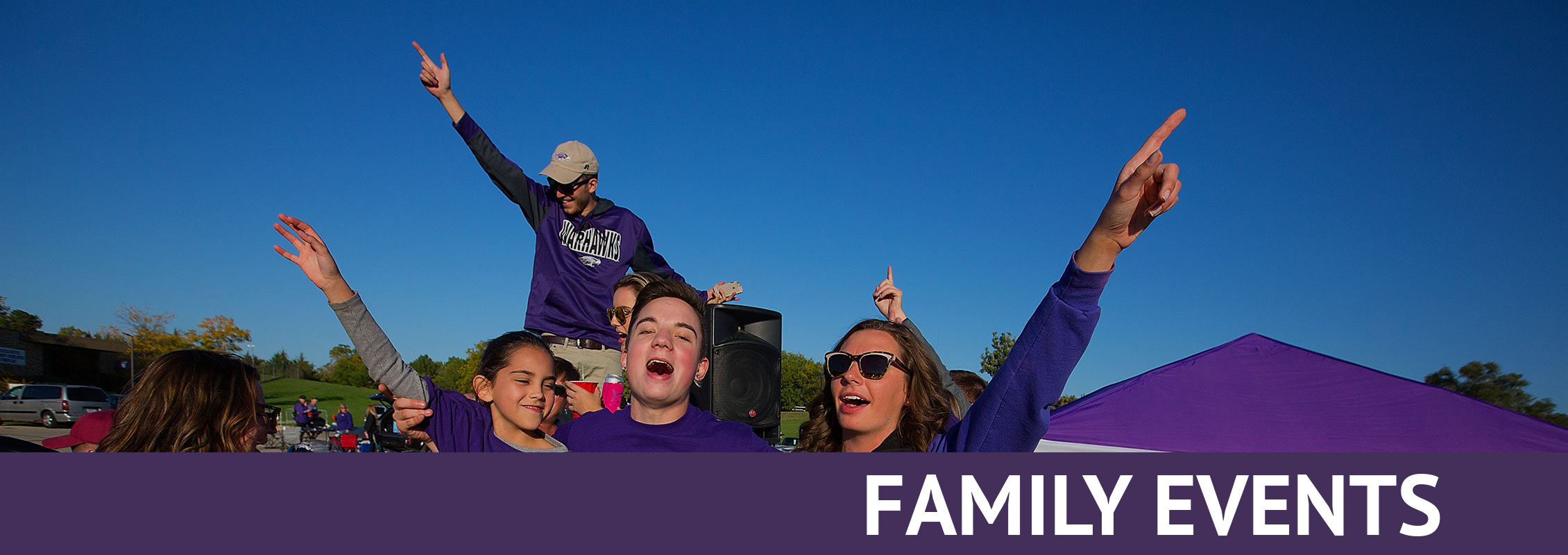 Family Events: A family dressed in purple singing or shouting, arms in the air