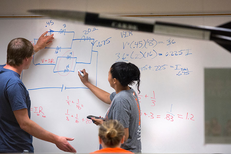 Physics students taking a test on a whiteboard