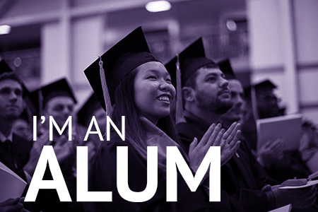 I'm an Alum: Students seated in cap and gown at commencement, applauding