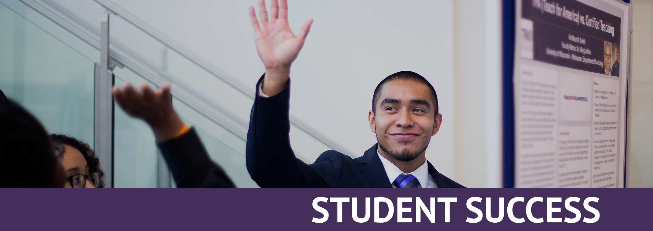 Student Success: A smiling student in a suit with his hand raised in front of his research project