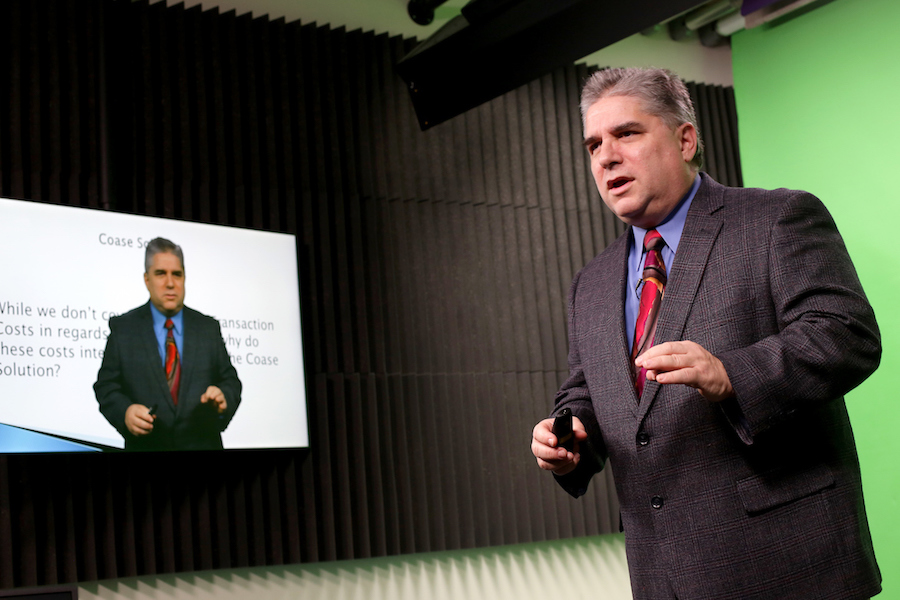 Image: Professor standing in front of a gren screen super imposed onto a powerpoint slide.