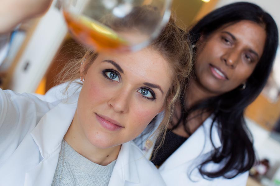 Image: A student and professor in a chemistry lab holding a test tube.